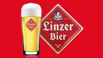 Linzer Bier Glas und Schild vor rotem Hintergrund